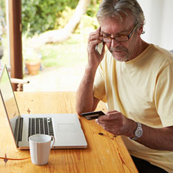 old-man-calling-while-holding-credit-card